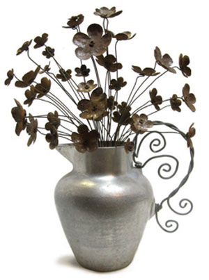 A Delicate Bouquet Of Metal Flowers Spills Over Vase
