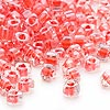 Seed bead, Miyuki, glass, clear color-lined coral, (TR1111L), #5 triangle. Sold per 250-gram pkg.